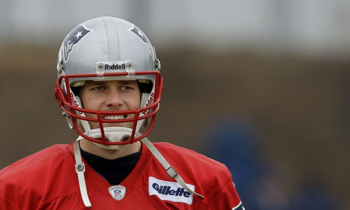 New England Patriots quarterback Tom Brady (12) smiles during a drills and stretching session before practice begins at the NFL football team's facility in Foxborough, Mass., Thursday, Jan. 16, 2014. The Patriots will play the Denver Broncos in the AFC Championship game Sunday in Denver. (AP Photo/Stephan Savoia)