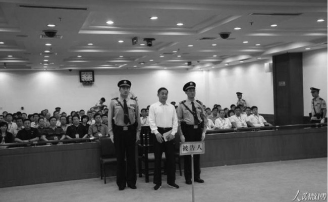 Bo Xilai stands between two officers at the court in Jinan, the capital of Shandong Province, on Sunday Sept 22. The arrest of Bo Xilai in March 2012 marked the beginning of a campaign to break the power of the Chinese regime's massive domestic security apparatus. (Weibo.com)