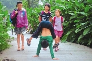 Yan Yuhong walks on his hands near his village. It takes him more than an hour to get to school every day. (Weibo.com)