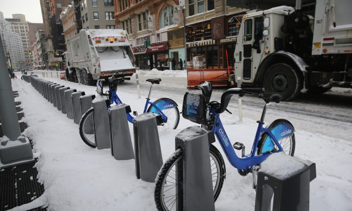 Garbage trucks plow past a Citi Bike station after a winter storm in New York City on Jan. 3, 2014. (John Moore/Getty Images)