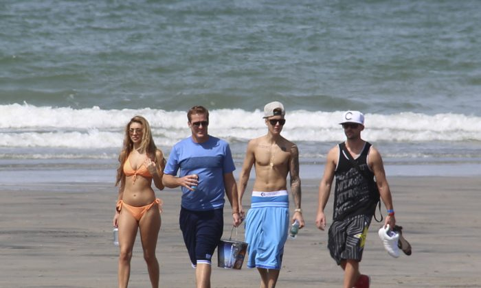 Justin Bieber, second right, and Chantel Jeffries, far left, walk with unidentified people on a beach in Punta Chame, Panama, Saturday, Jan. 25, 2014. (AP Photo/Eddy Vasquez)