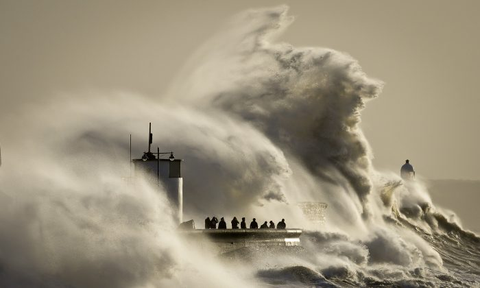 People watch and photograph enormous waves as they break, on Porthcawl harbour, South Wales, Monday Jan. 6, 2014.  (AP Photo/PA, Ben Birchall)