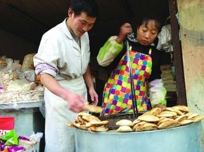 Baker Li Fugui and wife Fu Ling hard at work preparing baked cakes. (web photo)