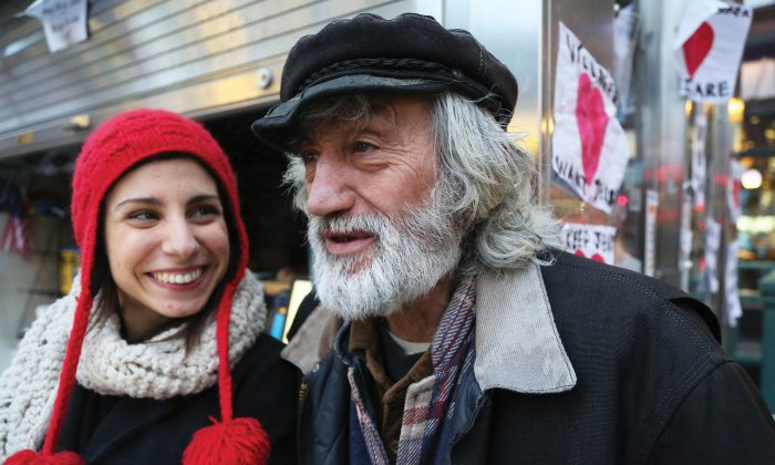 Jerry Delakas outside his newsstand at Astor Place as Nicole Cimino, maker of a documentary about Delakas's struggle to get his newsstand back, smiles at him, in Lower Manhattan, New York, on Jan. 14, 2014. (Ivan Pentchoukov/Epoch Times)