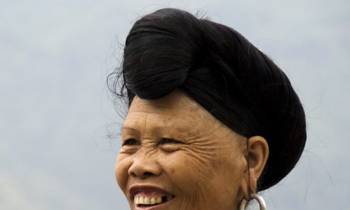 A Yao woman displays her hair styled in a bun over her forehead. The Yao women believe that the fermented rice water helps keep their hair black up past the age of 80. (Tim Whiteaker)