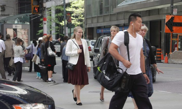 Pedestrians cross an intersection in downtown Toronto. Financial realities and lifestyle options are compelling young Canadians to live in the downtown cores of the country's cities, a new study finds. (The Canadian Press/Colin Perkel)