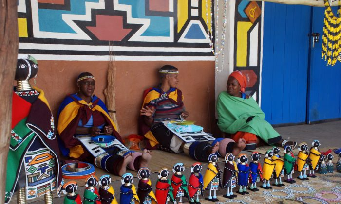 African ndebele women wearing traditional handmade accessories sell traditional dolls in Lesedi African Lodge and Cultural village, South Africa. (InnaFelker / Shutterstock.com)