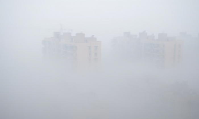 Two apartment buildings are barely visible in heavy smog in Hangzhou City, in southern China's Zhejiang Province, on Jan. 30. China's Central Meteorological Station sent out heavy fog alerts to 11 provinces in eastern, southern and central China. (Weibo.com)