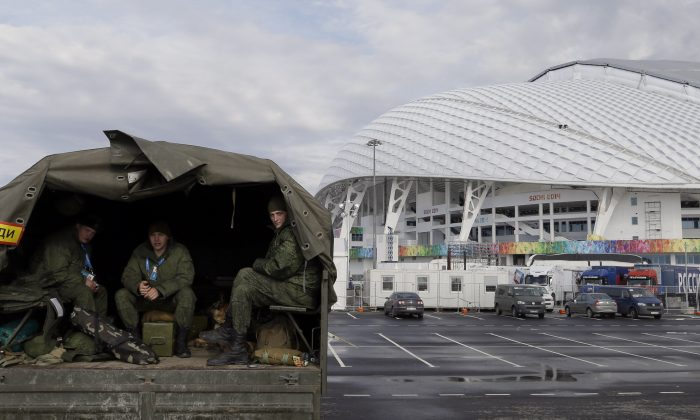 Security personnel sit in the back of a truck outside the Fisht Olympic Stadium in Sochi, Russia, Jan. 27, 2014. (AP Photo/David J. Phillip)