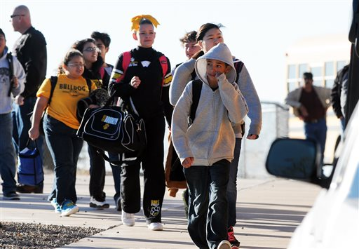 Students are escorted from Berrendo Middle School after a shooting, Tuesday, Jan. 14, 2014, in Roswell, N.M. A shooter opened fire at the middle school, injuring at least two students before being taken into custody. Roswell police said the school was placed on lockdown. (AP Photo/Roswell Daily Record, Mark Wilson)
