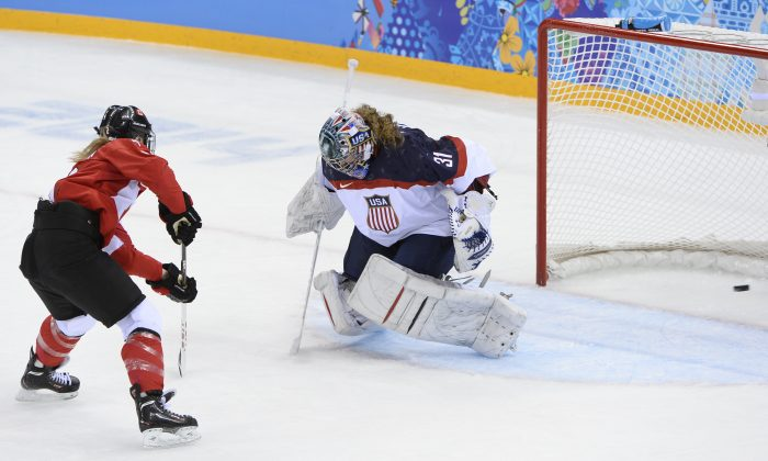 Canada's Meghan Agosta-Marciano (L) scores a goal past U.S. goalkeeper Jessie Vetter during the Women's Ice Hockey Group A match between Canada and USA at the Sochi Winter Olympics on February 12, 2014 at the Shayba Arena. (Jonathan Nackstrand/AFP/Getty Images)