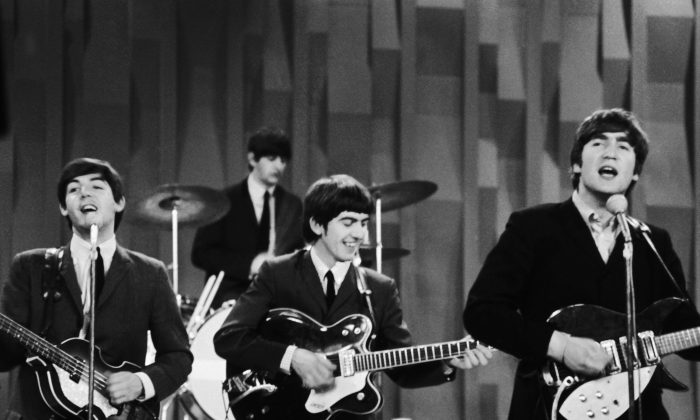 """The Beatles perform on the CBS """"Ed Sullivan Show"""" in New York on Feb. 9, 1964. Ringo Starr on drums, playing guitars (L–R) Paul McCartney, George Harrison, and John Lennon. (AP Photo/Dan Grossi/ file)"""