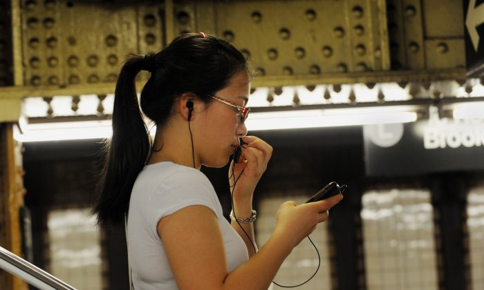 A woman use her smartphone on a subway platform in New York City (file photo). (STAN HONDA/AFP/Getty Images)