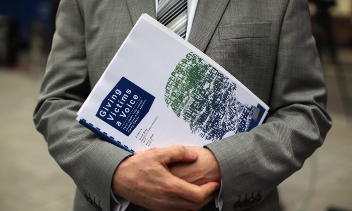 A reporter holds a copy of a report into the sexual allegations of the late TV star, Jimmy Savile outside New Scotland Yard on January 11, 2013 in London, England. (Dan Kitwood/Getty Images)