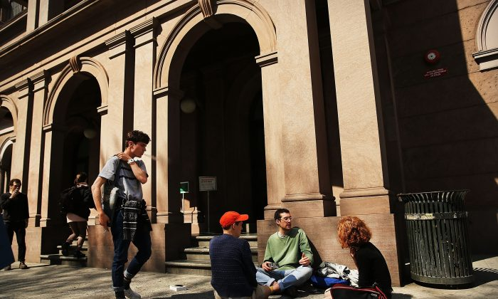 Students sit in front of Cooper Union for the Advancement of Science and Art, one of the last tuition-free colleges in the country, on April 24, 2013. (Photo by Spencer Platt/Getty Images)