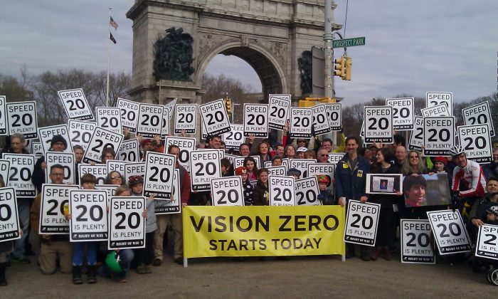 "Community members hold signs, reading  ""20 is Plenty,"" in support of New York state legislation to lower New York City speed limits to 20 mph, in Prospect Park, Brooklyn, New York, Feb. 2, 2014. (Catherine Yang/Epoch Times)"