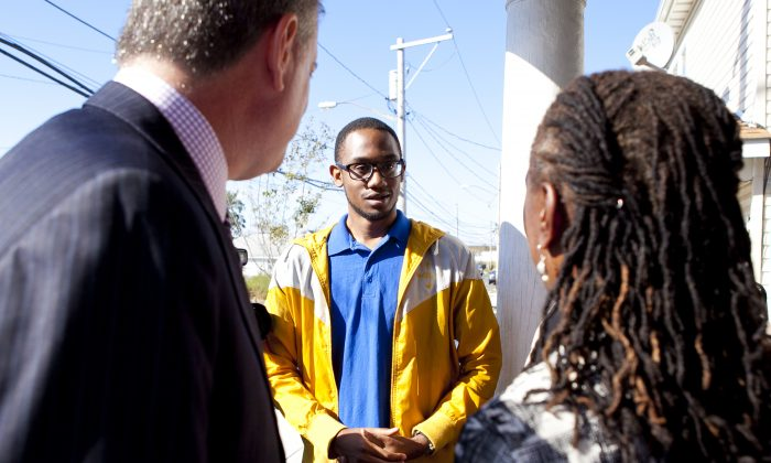 Bill de Blasio and Chirlane McCray speak with Bennett Bennett in Far Rockaway, Queens, New York, on Sept. 29, 2013. Bennett's family has spent their savings, retirement, and college funds to rebuild their Superstorm Sandy-damaged home. (Samira Bouaou/Epoch Times)