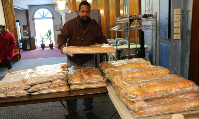 A volunteer brings trays of sandwiches into the Mount Vernon Baptist Church in Newark, N.J., Feb. 3, 2014. (Seth Hirsch)