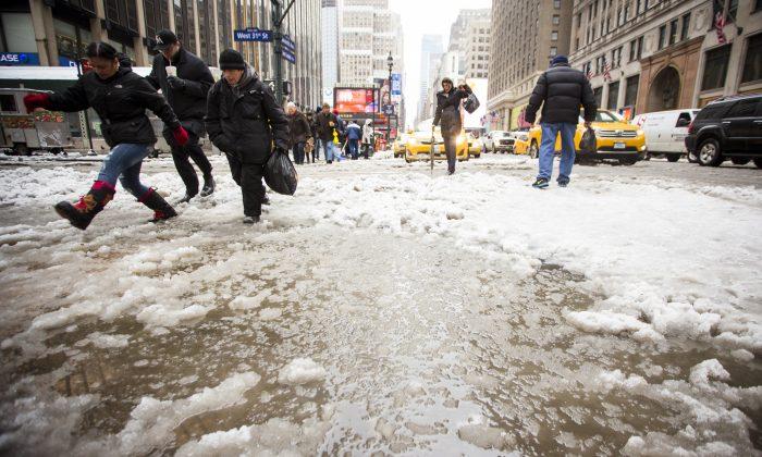 People navigate past a slush lake on 7th Avenue, near New York Penn Station in Midtown Manhattan, New York, Feb. 5, 2014. (Edward Dai/Epoch Times)