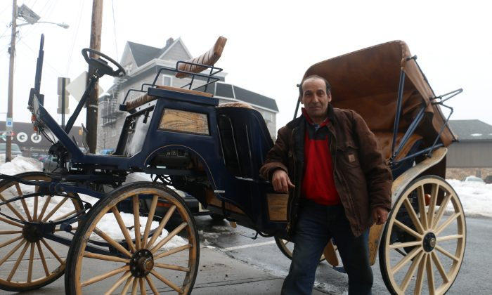 Alex Girami poses with the carriage he retrofitted to work with a battery instead of a horse in North Bergen, N.J., Feb. 21, 2014. (Allen Xie)