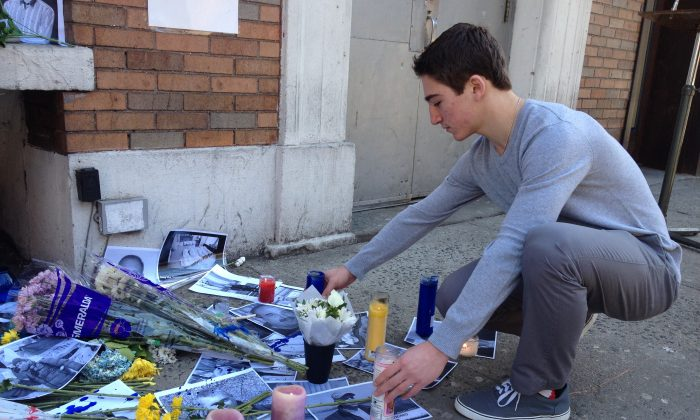 Marko Cohen, 14, lights candles at the memorial for protesters killed in Kyiv, Ukraine, in front of the American Ukrainian Youth Association (UAYA) building in East Village in New York on Feb. 23, 2014. (Kristina Skorbach/Epoch Times)