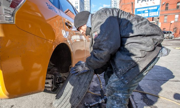 A man changes a flat tire on a taxi at a shop on 10th Avenue in Manhattan, New York, on Feb. 26, 2014. Damaged roads are costing each New York driver on average about $2,300 per year. (Petr Svab/Epoch Times)