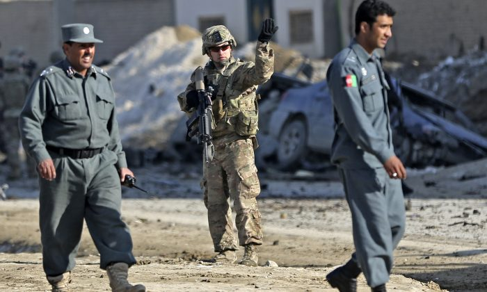 A U.S. soldier, center, directs traffic at the site of a suicide attack that struck near a NATO convoy in the Afghan capital Kabul, Afghanistan, Monday, Feb. 10, 2014. Taliban-affiliated militants have stepped up attacks in the final year of the international coalition's 13-year combat mission in Afghanistan, seeking to shake confidence in the Kabul government's ability to keep order after they assumed full security responsibility last year. (AP Photo/Massoud Hossaini)