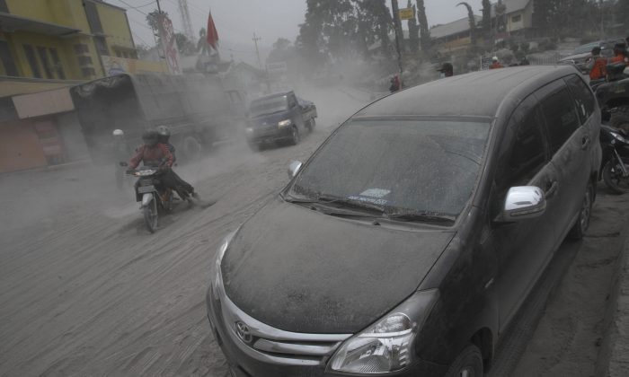Vehicles and a street are covered with volcanic ash from an eruption of Mount Kelud in Malang, East Java, Indonesia, Saturday, Feb. 15, 2014.  (AP Photo/Trisnadi)