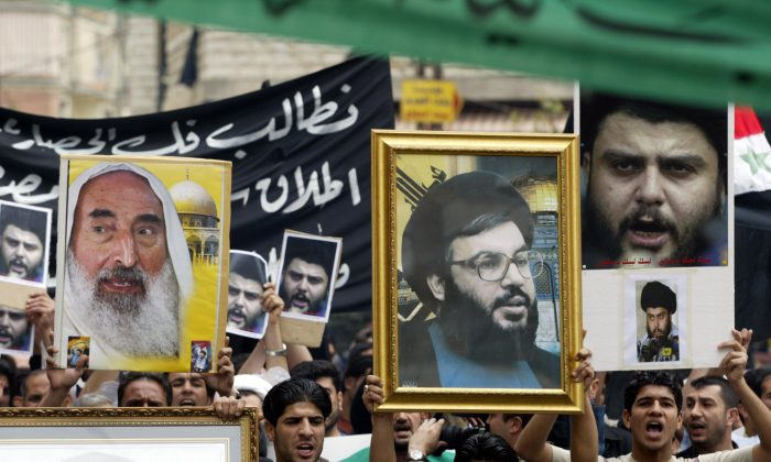 Iraqis Shiite protesters carry up pictures of late Hamas spiritual leader Sheikh Ahmed Yassin (L), Hezbollah secretary general Sheikh Hassan Nasrallah (C) and Iraqi Shiite cleric Moqtada al-Sadr during a demonstration in support of Sadr on 6 April, 2004, in the southern suburbs of Beirut. (JOSEPH BARRAK/AFP/Getty Images)
