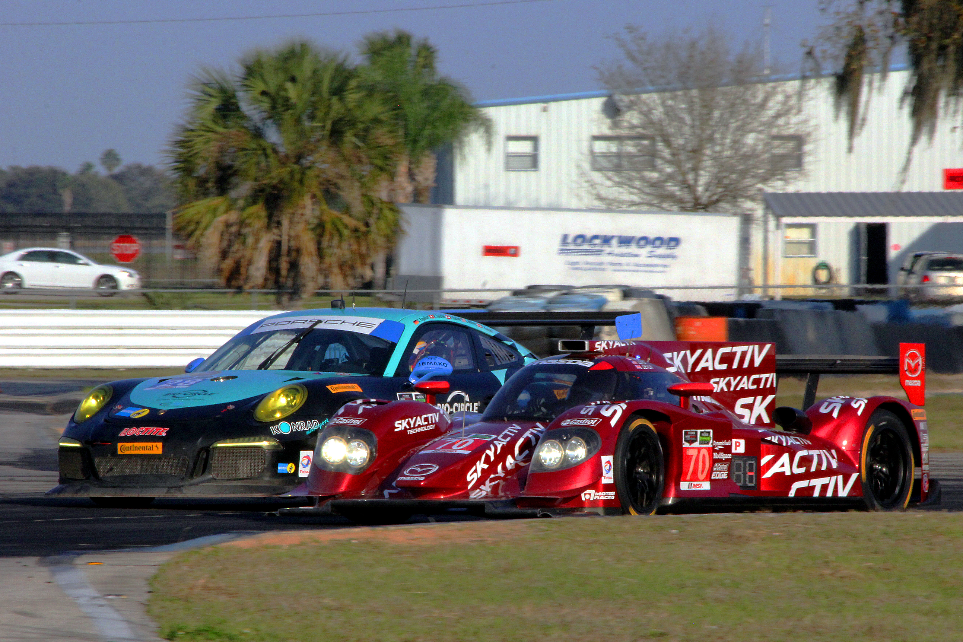 The #70 SpeedSource Mazda SkyActiv diesel P2 squeezes inside the #28 Dempsey Racing GTD Porsche at Turn Five Thursday afternoon. (Chris Jasurek/Epoch Times)