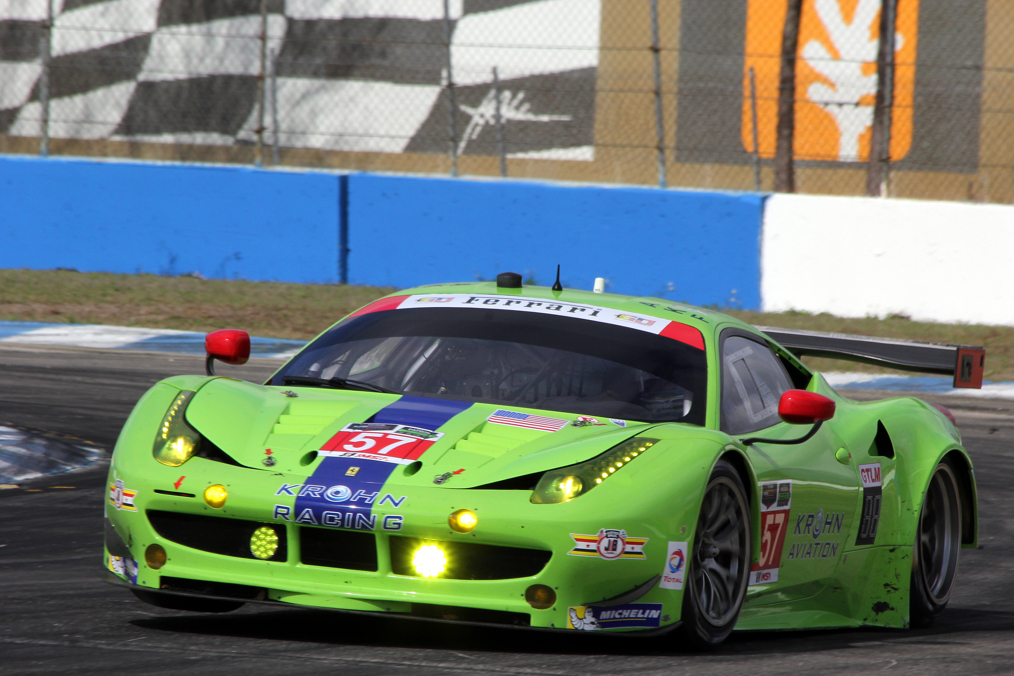 The #57 Krohn Racing Ferrari 458 proves that not only Porsches can lift a wheel around Turn Ten. (Chris Jasurek/Epoch Times)