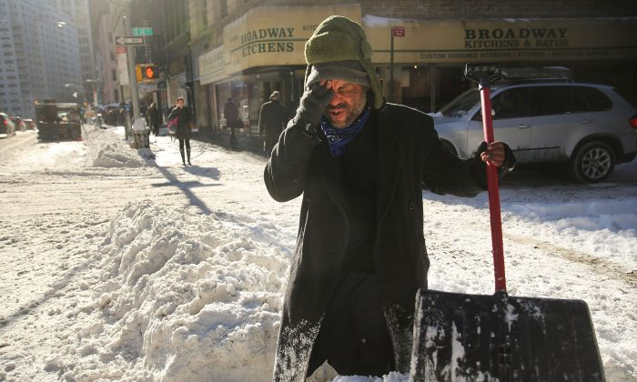 Diego Ramos, who is homeless and lives under nearby building scaffolding, pauses as he clears a sidewalk of snow in Lower Manhattan following a snow storm that left up to eight inches of snow in New York City, Jan. 3, 2014. (Spencer Platt/Getty Images)