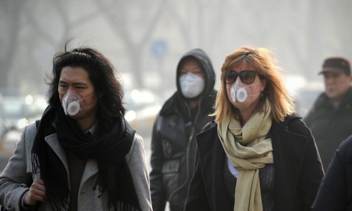 People wearing face masks walk along a street in Beijing on Jan. 16, 2014. Chinese scientists have found 1,315 species of inhalable micro-organisms in the polluted air of the nation's capital city. (Wang Zhao/AFP/Getty Images)