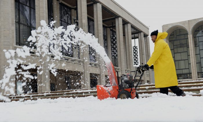 A man uses a snow blower to clear steps leading to Lincoln Center in New York after an overnight storm dropped more snow in the area, Feb. 5, 2014. (STAN HONDA/AFP/Getty Images)