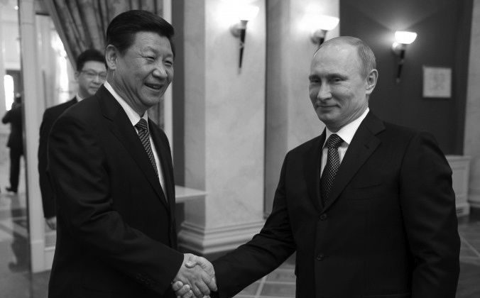 """Russia's President Vladimir Putin (R) shakes hands with Chinese Communist Party head Xi Jinping prior to a reception before the 2014 Winter Olympic Games opening ceremony in Sochi, on Feb. 7. Chinese Communist Party mouthpiece People's Daily reported that Xi's visit to Sochi was a sign of the """"special bond"""" between the two nations. (ALEXEI NIKOLSKY/AFP/Getty Images)"""