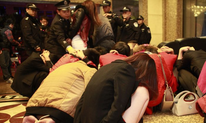 Chinese police round up alleged sex workers and clients at an entertainment center in Dongguan, in southern China's Guangdong province on Feb. 9, 2014. Raids on several venues involved in the illegal sex trade were shut down after China Central Television revealed a dozen hotels in Dongguan offered sex services. (STR/AFP/Getty Images)