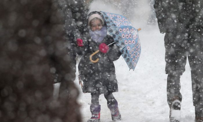 A child holds an umbrella as she walks to school during a snowstorm in New York City, Feb. 13, 2014. (John Moore/Getty Images)