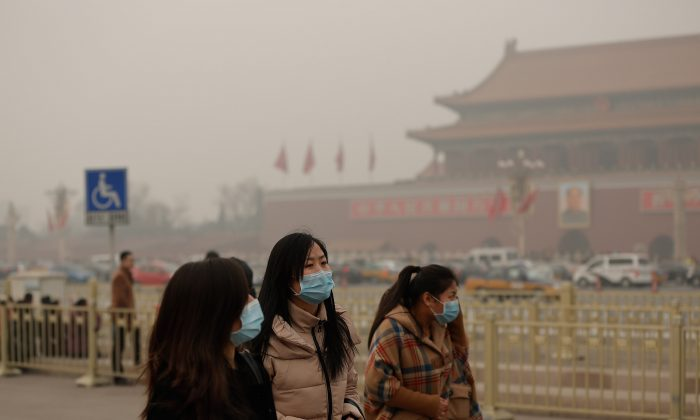 People walking on Tiananmen Square are wearing masks during severe pollution on Feb. 25, 2014 in Beijing, China. Emergency rooms for intravenous infusions and resuscitations have been overflowing with patients. (Lintao Zhang/Getty Images)