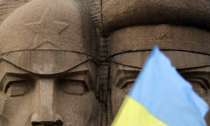 A Ukrainian flag flies in front of the KGB officers monuments in Kiev, Ukraine, Feb. 23, 2014. The acting government. (AP Photo/Darko Vojinovic)