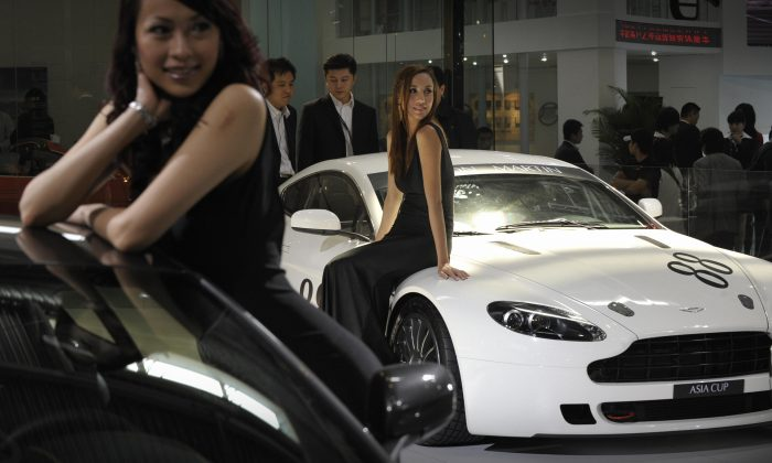 Models poses next to Aston Martin sportscars at the Beijing Auto Show in this file photo.  Aston Martin said it discovered that a Chinese subsidiary contractor was using lower quality and fake plastic for the accelerator pedal arms.(Peter Parks/AFP/Getty Images)