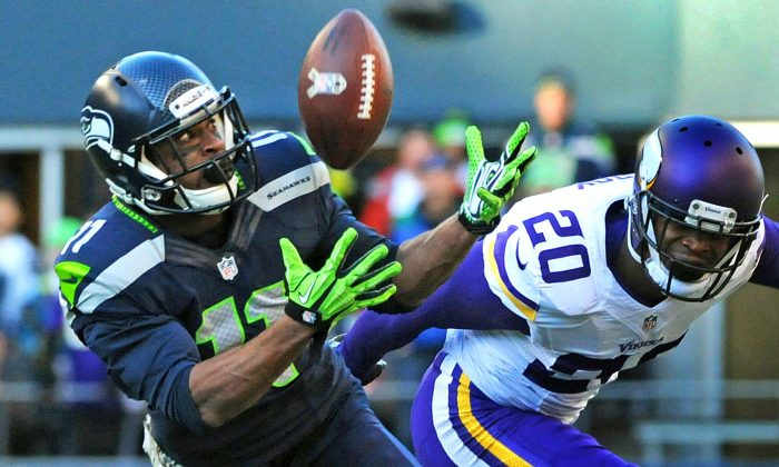In this Nov. 17, 2013, photo, Seattle Seahawks wide receiver Percy Harvin catches a 17-yard pass from quarterback Russell Wilson as Minnesota Vikings cornerback Chris Cook, right, defends during an NFL football game in Seattle. The catch was Harvin's only reception of the regular season. Harvin was cleared to play in this Sunday's Super Bowl after passing the NFL's concussion protocol, following a head injury suffered in Seattle's NFC divisional playoff game against New Orleans (AP Photo/Pioneer Press, Scott Takushi)  MINNEAPOLIS STAR TRIBUNE OUT  MAGS OUT   NOV. 17, 2013, PHOTO