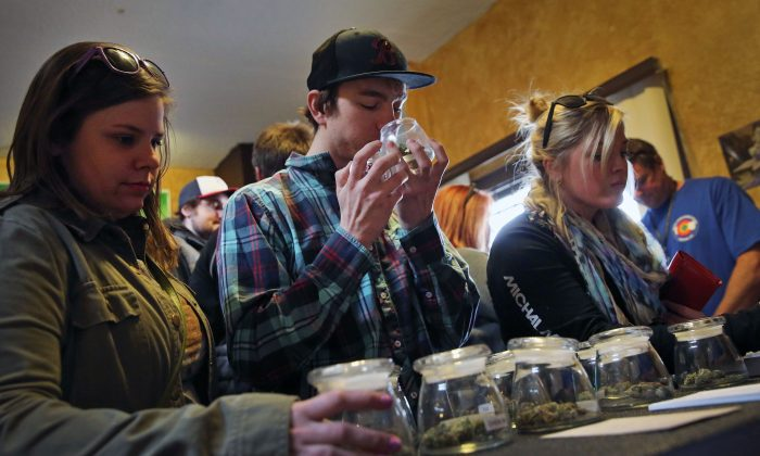 Customers, left to right, Alli Bertucci, Patrick Bean, and  Ali Regan shop for marijuana inside the retail store at 3D Cannabis Center, in Denver, Friday Feb. 14, 2014. (AP Photo/Brennan Linsley)
