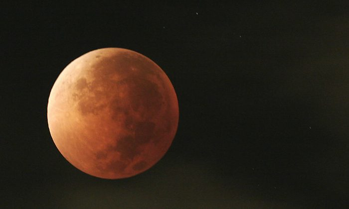 The moon is seen taking different orange tones during a lunar eclipse over Mexico City, Tuesday, Aug. 28, 2007. The event was widely visible from the United States and Canada as well as South America, the Pacific Ocean, western Asia and Australia. During a total lunar eclipse, the moon's disk can take on a colorful appearance from bright orange to blood red to dark brown and, rarely,  very dark gray. (AP Photo Marco Ugarte)