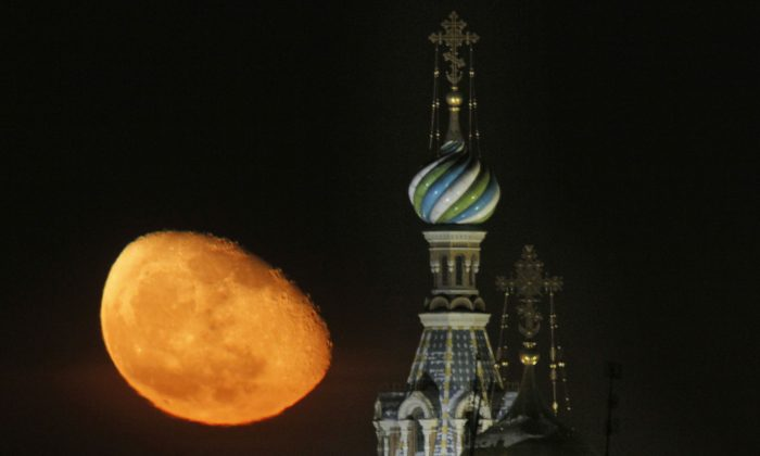 The moon rises above the Savior of Spilled Blood Cathedral in downtown  St.Petersburg, Russia, Sunday, Feb. 12, 2012. (AP Photo/Dmitry Lovetsky)
