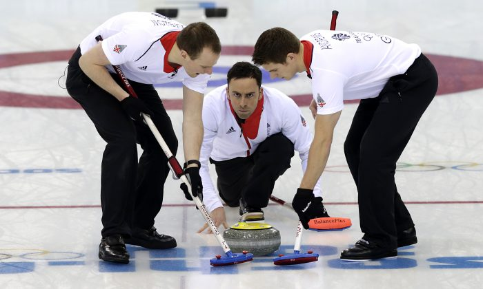 Britain's David Murdoch, center, watches the rock while Michael Goodfellow, left and Scott Andrews sweep the ice during the men's tiebreaker curling match against Norway at the 2014 Winter Olympics, Tuesday, Feb. 18, 2014, in Sochi, Russia. (AP Photo/Wong Maye-E)