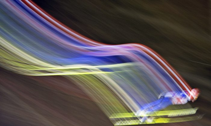 In this picture taken with a time exposure Richard Freitagi of Germany soars through the air during the qualification at the FIS World Cup ski jumping in Willingen, Germany, Friday, Jan. 31, 2014. (AP Photo/Jens Meyer)