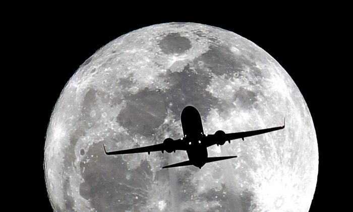 """An airplane passes the full moon, known in the Farmers' Almanac as the """"Wolf Moon,"""" on its final approach to Los Angeles International Airport over Whittier, Calif. on Wednesday, Jan. 15, 2014. (AP Photo/Nick Ut)"""