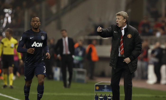 Manchester United's coach David Moyes , right, gives instructions to his players during a Champions League, round of 16, first leg soccer match  against Olympiakos at Georgios Karaiskakis stadium, in Piraeus port, near Athens, on Tuesday, Feb. 25, 2014. (AP Photo/Petros Giannakouris)