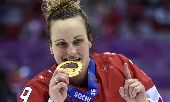 Canada's Marie-Philip Poulin bites her gold medal after scoring the winning goal in overtime to beat the USA 3-2 for the gold medal in women's hockey at the Sochi Winter Olympics Friday, Feb. 21, 2014 in Sochi. (AP Photo/The Canadian Press, Paul Chiasson)