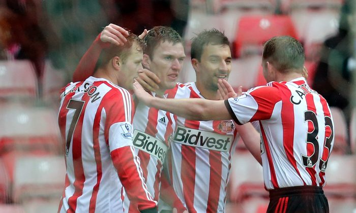 Sunderland's Craig Gardner, second left, celebrates his goal with his teammates during their English FA Cup fifth round soccer match against Southampton at the Stadium of Light, Sunderland, England, Saturday, Feb. 15, 2014. (AP Photo/Scott Heppell)